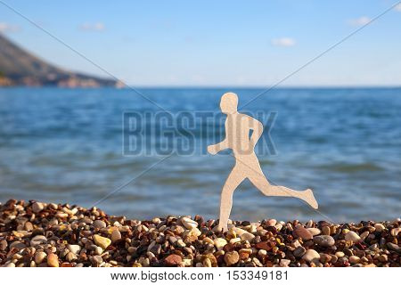 White paper male figure on a gravel beach poster