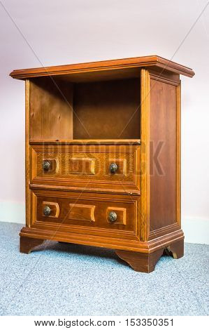 Wooden antique nightstand on the light background in the room
