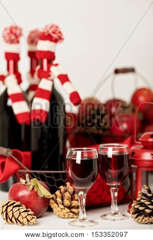 Merry Christmas and happy New year. Bottles of wine in a knitted Santa hats glasses and basket of apples.