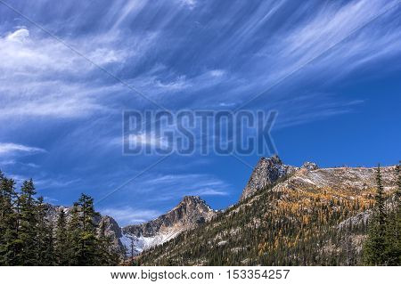 Two mountain peaks under a blue sky with streaking clouds along highway 20 in the Washington Cascades.