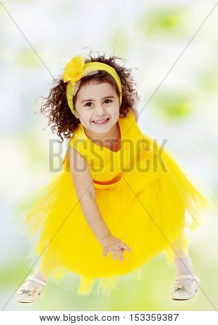 Happy little curly girl in a bright yellow dress, dancing happily.white-green blurred abstract background with snowflakes.