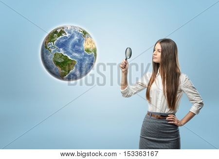 Full portrait of businesswoman looking at Globe Earth through a magnifier. Environment and ecology. Resource usage. Find useful resources. Search to benefit from natural resources. Elements of this image are furnished by NASA.