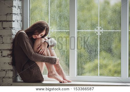 Beautiful young woman sitting alone near window with rain drops. Sexy and sad girl with long slim legs. Concept of loneliness.