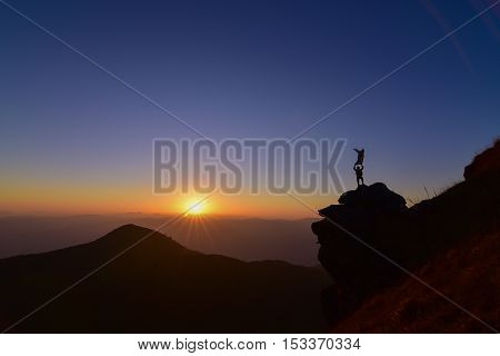 man standing on the rock on top of the mountain above sunset with waving his scarf for celebrate .