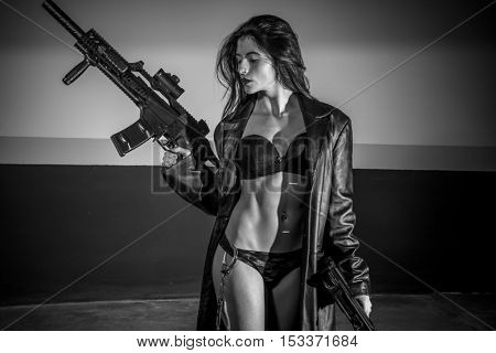 Fantasy brunette girl with long leather coat and lingerie with machine gun and pistol posing dangerous in a garage