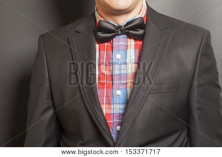 Man wearing a black suit and black bow tie on gray background