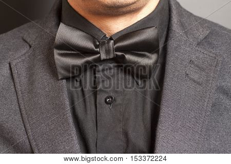 Man wearing a gray suit and black bow tie on gray background