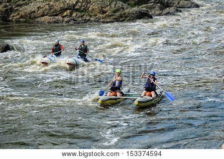 Beklenischevo, Russia - June 12, 2005: The place with the Iset River rapid current, a so-called threshold the Revun - Howler. Woman on sports catamaran for two on speed river