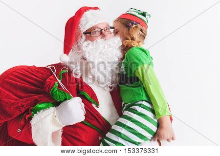 Christmas Wish 2016. Santa Claus and Little Girl Elf. Telling Wishes in Santa Claus's Ear. Cristmas Scene at White Background