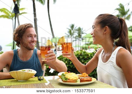 Happy multiracial couple toasting cheers with alcoholic hawaiian drinks, Mai Tai, Hawaii experience. Summer travel holidays, people enjoying local food meal at outdoor terrace restaurant of resort.