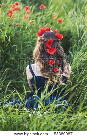 Beautiful young woman on the poppy field backview