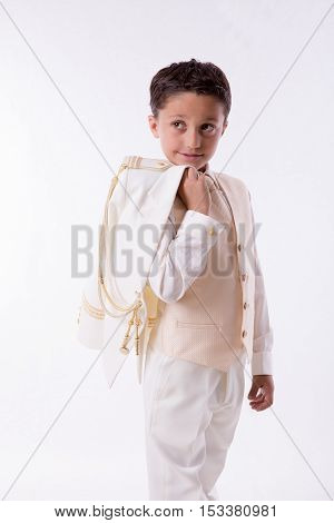 Young First Communion boy with his jacket over his shoulder on white background