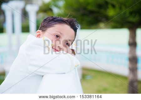 Young boy with white suit smiling and leaning on a white wooden fence in his First Communion