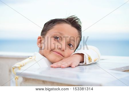 Young boy with white suit leaning on a wall with his head over his hand in his First Communion. Shallow depth of field.