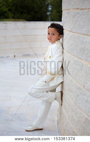 Young boy with white suit leaning on a wall with one foot in his First Communion.