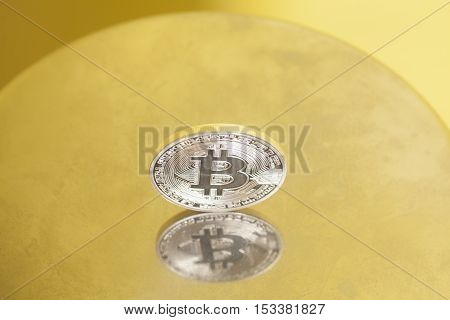 silver bitcoin coin on a metal surface