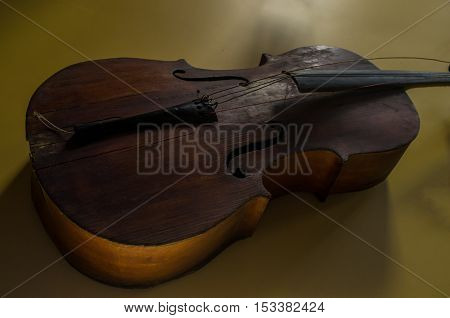 Old worn vintage cello hanging on yellow wall
