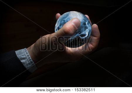 Hand holding magic crystal ball filled with smoke