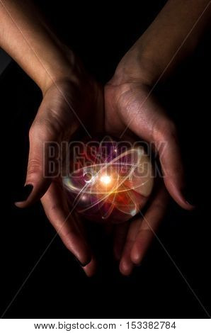Female hands hold crystal ball with atom particle for fortune telling background