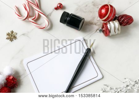 Over head flat lay desktop of Christmas items. Blank stationary, pen and ink, candy,  and tree trimmings in red and white.