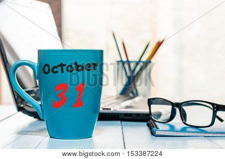 October 31st. Day 31 of month, calendar on hot coffee cup at translator or interpreter workplace background. Autumn time. Empty space for text.