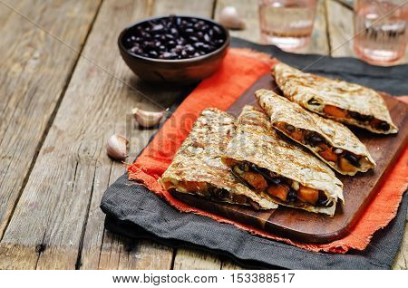 Black beans spiced sweet potato quesadilla on wood background