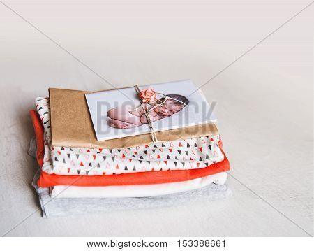 Printed greeting card with cutest sleeping newborn baby with baby clothes. Dream about baby. Waiting for the baby: preparing for congratulation.