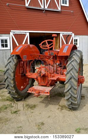 ROLLAG, MINNESOTA, Sept 1. 2016:A  restored Case tractor parked in front of a red barn is displayed at the West Central Steam Threshers Reunion in Rollag, MN attended by 1000's held annually on Labor Day weekend.