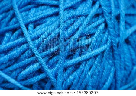 Woolen yarn ball, skein of tangled blue sewing threads, selective foci