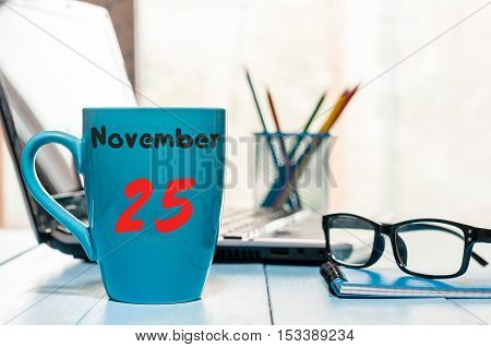 November 25th. Day 25 of month, calendar on green tea cup at Administrator workplace background. Autumn time. Empty space for text.