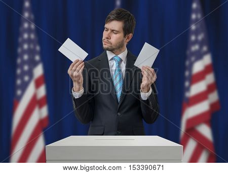 Election in United States of America. Undecided voter holds envelopes in hands above vote ballot and making decision. USA flags in background. Democracy concept.