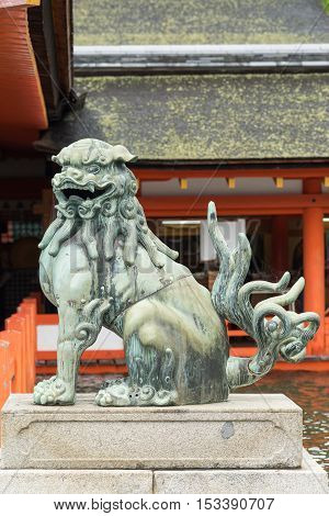 Hiroshima Japan - September 20 2016: Open mouth lion statue at itsukushima Shinto Shrine on Miyajima Island. Vermilion wood structures in back. Shrine is built on platforms in Inland Sea.
