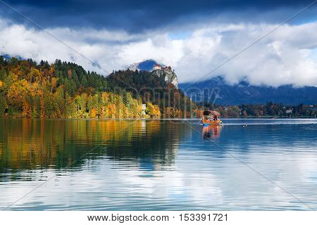 Amazing View On Bled Lake with Castle and Mountains in Background. Traditional wooden boats on Lake Bled Slovenia. Autumn in Slovenia Europe.
