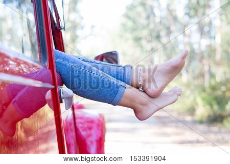 Woman on a roadtrip relaxing in her convertible car