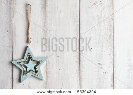 Wooden star-shaped christmas decoration hanging over white fence