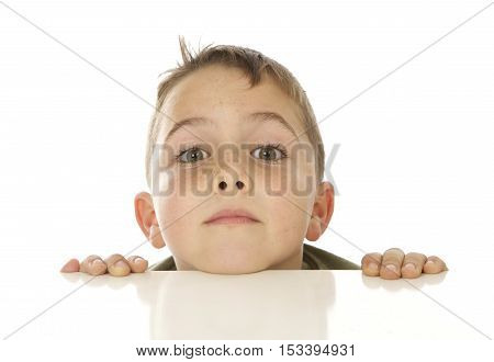 Cute Seven Year Old Boy Peeking Up over a White Table on a White Background with a funny expression