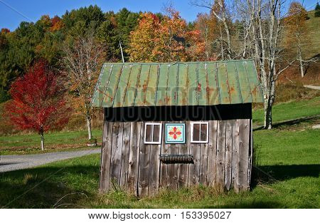 a small rustic shed with a quilt pattern, in autumn