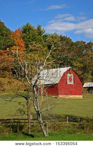 a bright red barn with a quilt square set against a hillside with trees changing colors in autumn