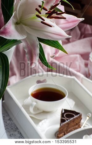 Flowers and buds pink and white lilies. Backlight. The rays of the sun through the wooden blinds. Selective focus. Desserts and tea on white wooden dressing.