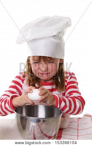Cute Little Girl With a Chef Hat and Apron Baking.  She is making a funny face as she concentrates on cracking an egg into a metal bowl.