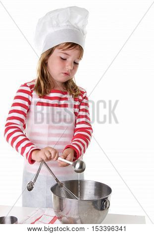 Cute Little Girl With a Chef Hat and Apron Baking. She is adding an ingredient with a measuring spoon