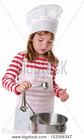 Cute Little Girl With a Chef Hat and Apron Baking. She is adding an ingredient with measuring spoons.