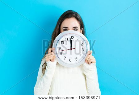 Woman Holding Clock Showing Nearly 12
