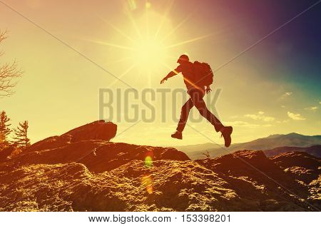 Man Jumping Over Gap On Mountain Hike