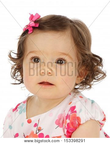 Cute baby girl on a white background with brown hair and brown eyes.