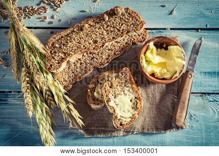 Delicious bread with butter for breakfast on old wooden table