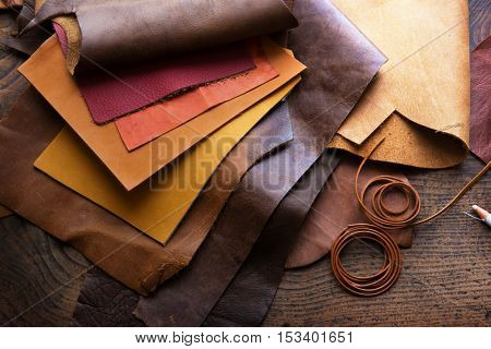 Leather craft or leather working. Selected pieces of beautifully colored or tanned leather on leather craftman's work desk.