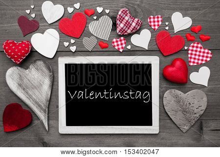 Chalkboard With German Text Valentinstag Mean Valentines Day. Red Textile Hearts. Grey Wooden Background With Vintage, Or Retro Style. Black And White Style With Colored Hot Spots