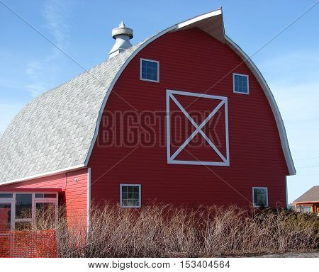 A red barn against a blue sky with cupola on top.