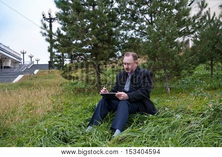 Man working with computer sitting outdoors in park